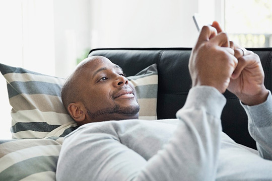 a man is sitting on a couch, browsing on his phone